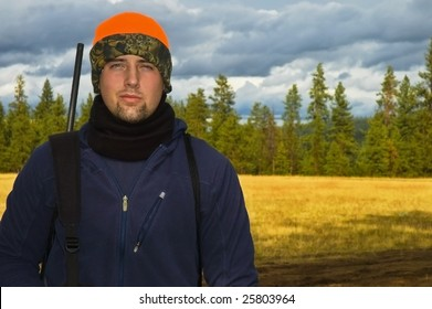 Portrait of a teenage hunter posed in front of a open meadow background.