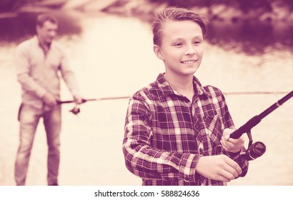 Portrait of teenager boy casting line for fishing on lake