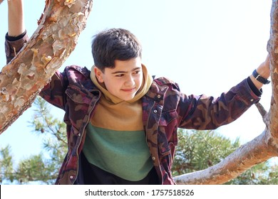 Portrait of teenager boy holding hands at tree against blue sky