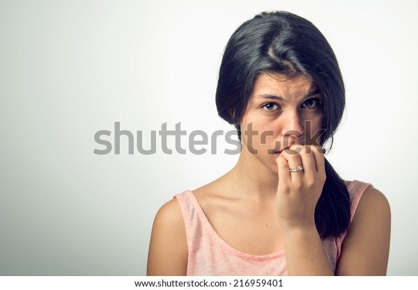 Portræt Af En teenager brunette pige med nervøst udtryk og neglebidende