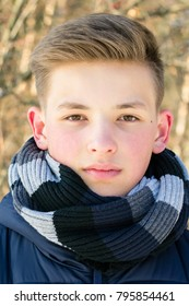 Portrait of a teenager close-up. The young guy. A teenager with a scarf on a winter day.