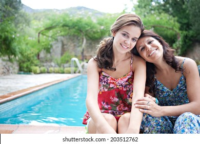 Portrait of a teenager daughter and her mother sitting and smiling during a summer holiday in a vacation home green garden at the edge of a swimming pool, relaxing together. Outdoors lifestyle.