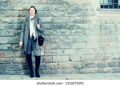 portrait of teenager girl in the historical city in hood near wall