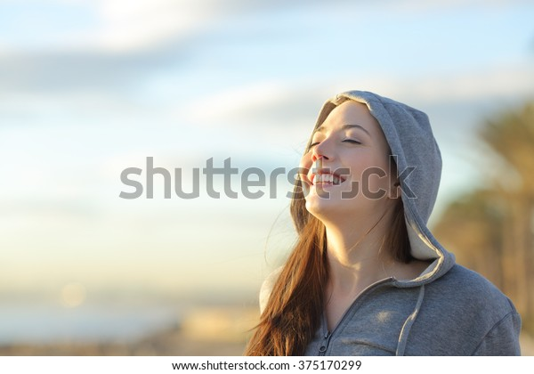 Portrait of a teenager girl wearing hood breathing deep fresh air on the beach at sunrise in a summer sunny day with a beautiful warm sky in the background