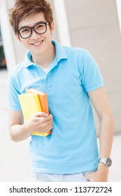 Portrait of a teenager in glasses holding books