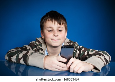 portrait of a teenager with a phone on a blue background
