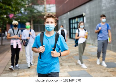 Portrait of teenager in protective mask with backpack going to school lessons on sunny autumn day. New lifestyle during coronavirus pandemic