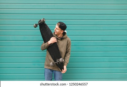 Portrait of a teenager in street clothes standing with a longboard in his hands on a turquoise background. Portrait of a young skater. Street culture.