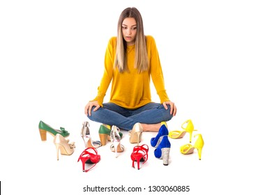 Portrait of a teenager woman sitting on the floor between many pairs of shoes against white. Consumerism concept