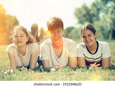 Portrait of teenagers lying on grass in park and looking happy