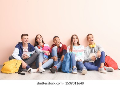 Portrait of teenagers sitting near color wall