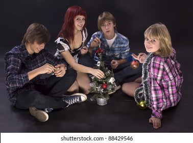 Portrait of teenagers with tiny Christmas tree