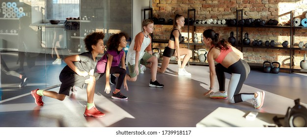 Portrait of teens, boy and girl warming up, exercising with female trainer in gym. Sport, healthy lifestyle, physical education concept. Horizontal shot. Selective focus. Web Banner