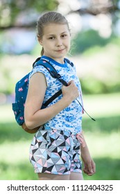 Portrait of ten year old Caucasian girl with small backpack on her back, summer garden