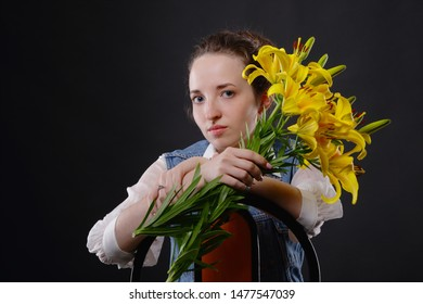 Portrait of a tender attractive girl with yellow lilies