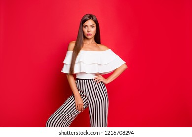 Portrait of tender content calm thin attractive magnificent lovable fascinating lady in striped pants isolated over bright vivid red background