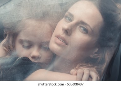 portrait of tender daughter and mother hugging with white veil