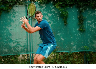 Portrait of a tennis player in action. Young man keeping a racket ready to hit a ball.