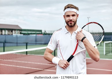 Portrait of tennis player man. Front view. Looking at camera. on the court