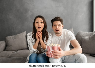Portrait of tense man and woman sitting on sofa at home and looking at you while watching scary movie and eating popcorn