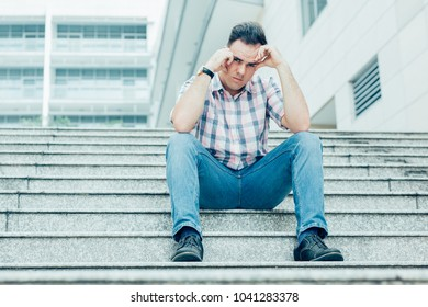Portrait of tensed young man leaning head on hands, looking at camera and sitting on stairway outdoors with building in background. Low angle front view.