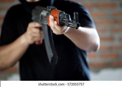 Portrait of terrorist holding assalt riffle close up.