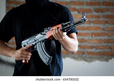 Portrait of terrorist holding assault riffle close up.