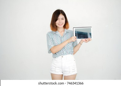 Portrait of thai adult beautiful girl short hair show her tablet.