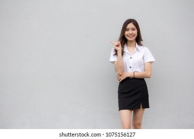 Portrait of thai adult student university uniform beautiful girl pointing