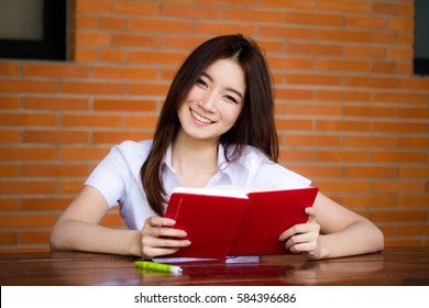 Portrait of thai adult student university uniform beautiful girl read red book