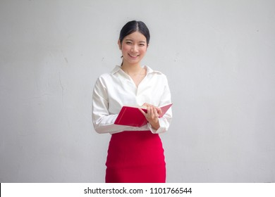 Portrait of thai adult working women white shirt red skirt reading red book