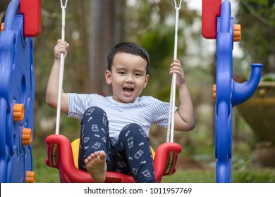 Portrait Thai boy play the swing in the playground in front of the house. He is cute and has a bright smile. Exercise in the morning for a healthy body. Soft focus and blur. Sport and game concept.