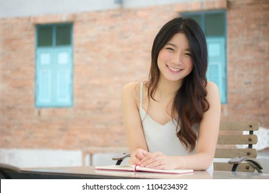Portrait of thai china adult beautiful girl White shirt blue jeans reading red book