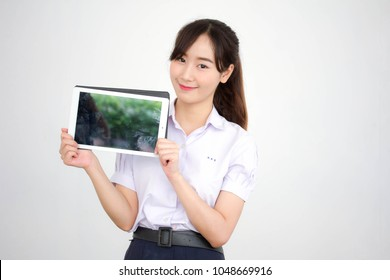 Portrait of thai high school student uniform beautiful girl using her tablet