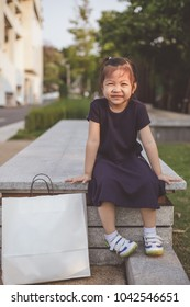 Portrait of thai kid  . smile of Cute little girl with shopping bags .