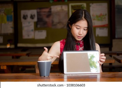 Portrait of thai teen beautiful girl in Chinese dress using her tablet