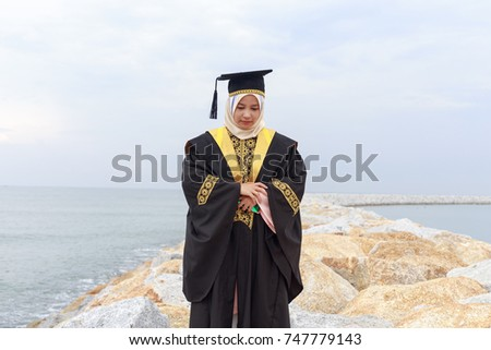 25873ba1852 Portrait of thankful young girl in hijab and graduation dress standing on  rocks beach side.