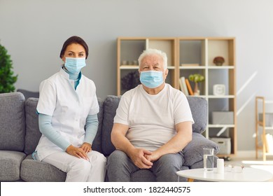 Portrait of therapeutist and aged white-haired man, both wearing medical face masks, sitting on couch at home. Female doctor visiting senior male patient during period of seasonal infections