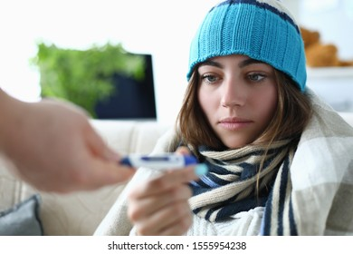 Portrait of thermal measuring utility used for finding out various sickness from common cold to severe flu. Woman in warm clothes trying cure body condition. Hard virus concept