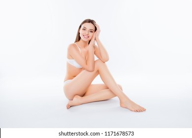 Portrait of thin slender woman sitting over white background in bra and bikini looking at camera demonstrating perfect body plain skin