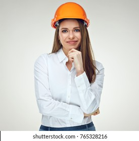 Portrait of thinking business woman wearing builder helmet isolated on white.