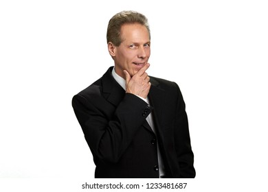 Portrait of thinking businessman on white background. Caucasian middle-aged man in formal wear looking flirtatiously. Flirty macho man on white background. Invitation for a date.
