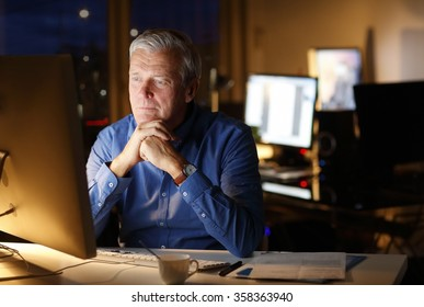 Portrait of thinking businessman sitting in front of computer at office and working late.