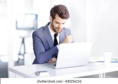 Portrait of thinking businessman sitting in the office and using his laptop while working on new project.
