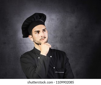 Portrait of a thinking chef cooker in black uniform, gray background