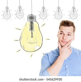 Portrait thinking handsome man looking up with idea light bulb above head isolated on white background