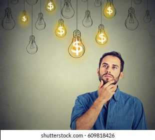 Portrait thinking handsome young man looking up at many dollar idea light bulbs above head