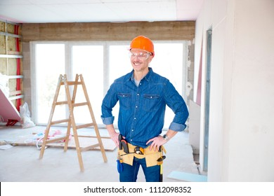 Portrait of thinking handyman wearing safety helmet and protective eye goggles while standing with hands on his hip at the construction site.