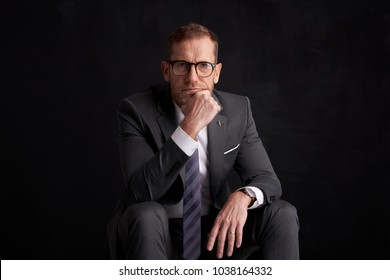 Portrait of thinking middle aged businessman sitting at dark background and looking thoughful.
