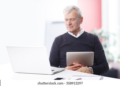Portrait of thinking old businessman working on laptop and holding in his hand a digital tablet while sitting at office.